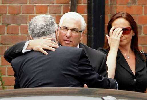 Mitch Winehouse, center, the father of British singer Amy Winehouse, is consoled as he arrives at Golders Green Crematorium, north London, Tuesday, July 26, 2011. The soul diva, who had battled alcohol and drug addiction, was found dead Saturday at her London home. She was 27.(AP Photo/Joel Ryan) Photo: Joel Ryan / AP