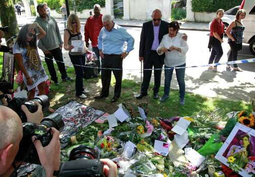 """Mitch Winehouse, center blue shirt, Amy Winehouse 's father, accompanied by Janis, Amy's mother, seen right white shirt and other friends, looks at flowers placed by mourners in Camden Square outside the house of Amy Winehouse following her death, in Camden, northern London, Monday July 25, 2011.  Mitch Winehouse greeted and thanked mourners for coming to lay bouquets and handwritten notes, only hours before police promised to release a post mortem on her death. """"This means so much to my family,"""" he said. The 27-year-old singer died Saturday after publicly struggling with drug and alcohol abuse for years. (AP Photo/Lefteris Pitarakis) Photo: Lefteris Pitarakis / AP"""