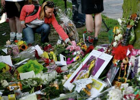 An unidentified woman leaves a floral tribute outside the home of singer Amy Winehouse in Camden Square, north London, Sunday, July 24, 2011. Amy Winehouse, the beehived soul-jazz diva whose self-destructive habits overshadowed a distinctive musical talent, was found dead Saturday, July 23, 2011 in her London home. She was 27. (AP Photo/Akira Suemori) Photo: Akira Suemori / AP