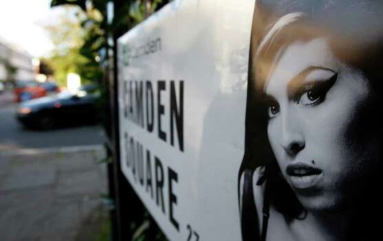 A picture of singer Amy Winehouse is seen stuck to an address sign as a car drives past it near the residence of Winehouse in Camden Square, north London, Sunday, July 24, 2011. Amy Winehouse, the beehived soul-jazz diva whose self-destructive habits overshadowed a distinctive musical talent, was found dead Saturday, July 23, 2011 in her London home. She was 27.(AP Photo/Akira Suemori) Photo: Akira Suemori / AP