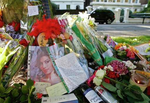 Floral tributes are seen outside the residence of singer Amy Winehouse in Camden Square, north London, Sunday, July 24, 2011. Amy Winehouse, the beehived soul-jazz diva whose self-destructive habits overshadowed a distinctive musical talent, was found dead Saturday, July 23, 2011 in her London home. She was 27.(AP Photo/Akira Suemori) Photo: Akira Suemori / AP