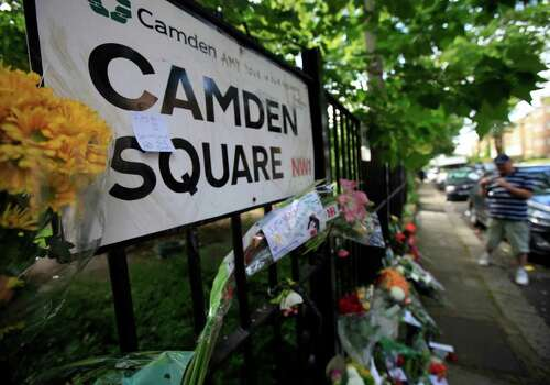 """Flowers and tributes left by mourners dercorate a street sign in Camden Square outside the house of Amy Winehouse following her death,  Monday July 25, 2011 Mitch Winehouse, Amy Winehouse 's father greeted and thanked mourners for coming to lay bouquets, messages and handwritten notes, only hours before police promised to release a post mortem on her death. """"This means so much to my family,"""" he said. The 27-year-old singer died Saturday afer publicly struggling with drug and alcohol abuse for years. (AP Photo/Lefteris Pitarakis) Photo: Lefteris Pitarakis / AP"""