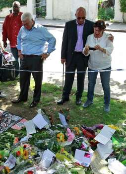 "Mitch Winehouse, 2nd left blue shirt, Amy Winehouse 's father, accompanied by Janis, Amy's mother, right, and other friends look at flowers placed by mourners in Camden Square outside the house of Amy Winehouse following her death, in Camden, northern London, Monday July 25, 2011.  Mitch Winehouse greeted and thanked mourners for coming to lay bouquets, messages and handwritten notes, only hours before police promised to release a post mortem on her death. ""This means so much to my family,"" he said. The 27-year-old singer died Saturday after publicly struggling with drug and alcohol abuse for years. (AP Photo/Lefteris Pitarakis) Photo: Lefteris Pitarakis / AP"