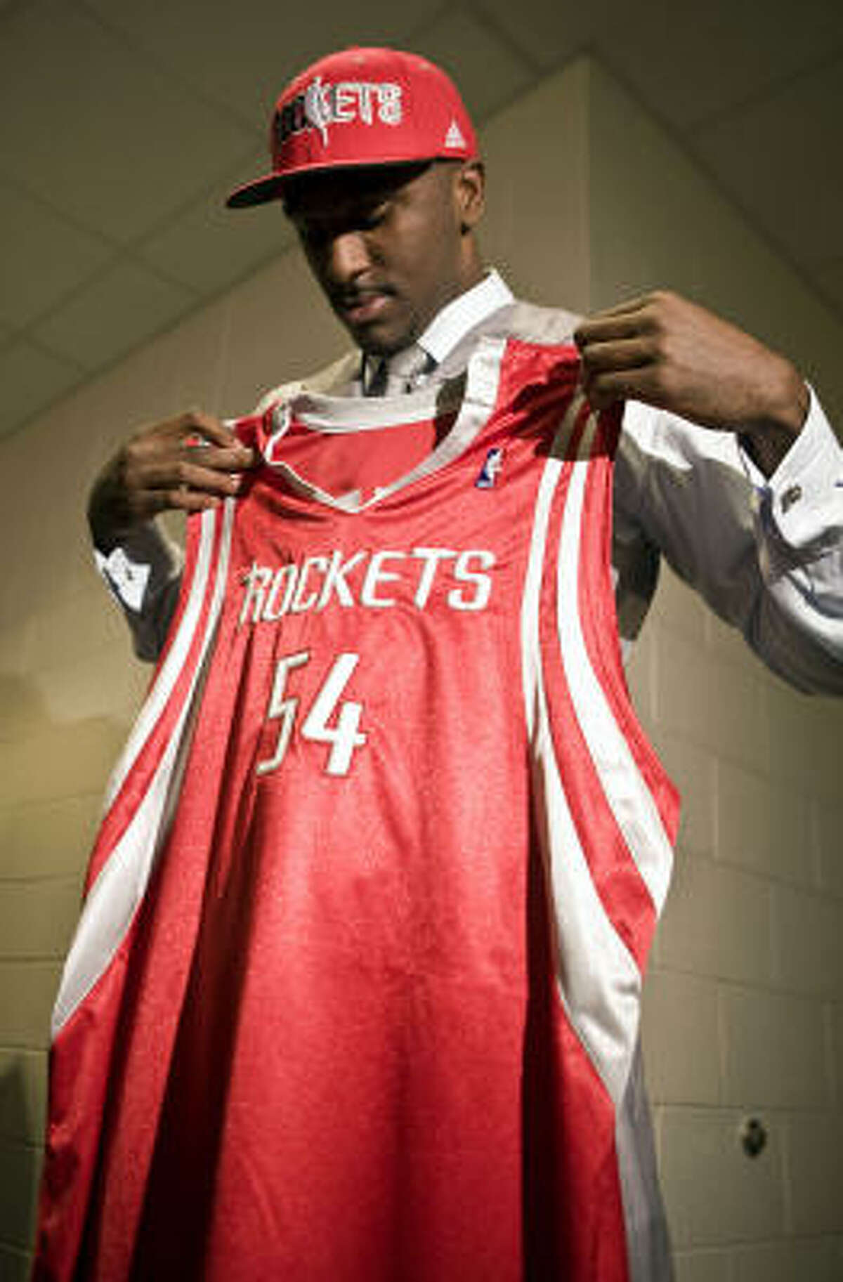 Rockets first-round pick Patrick Patterson looks over his jersey after addressing the media.