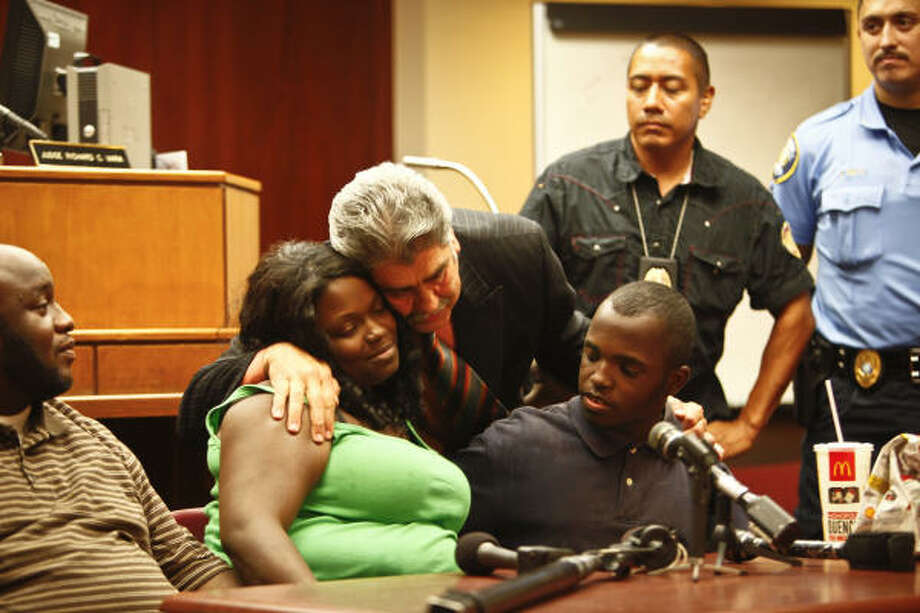 Harris County Precinct 6 Constable Victor Trevino hugs Sherri Johnson-Miller after she was reunited with her 13-year-old son, Kenneth, center, who was missing for four days. Photo: Michael Paulsen, Chronicle