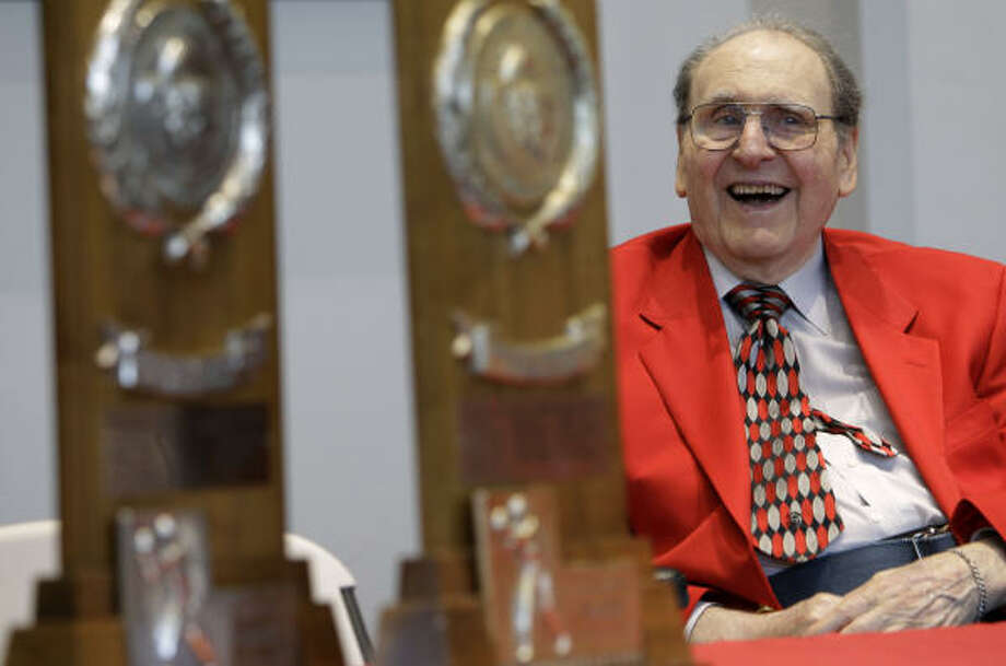 Former UH basketball coach Guy V. Lewis looks at two of his five NCAA Final Four trophies during Friday's reception held in his honor. Photo: Charlie Neibergall, AP