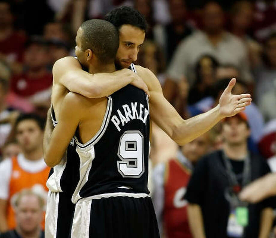 In a mix of relief and joy, Spurs guards Tony Parker (9) and Manu Ginobili embrace at the end of Game 3. Photo: Gregory Shamus, Getty Images