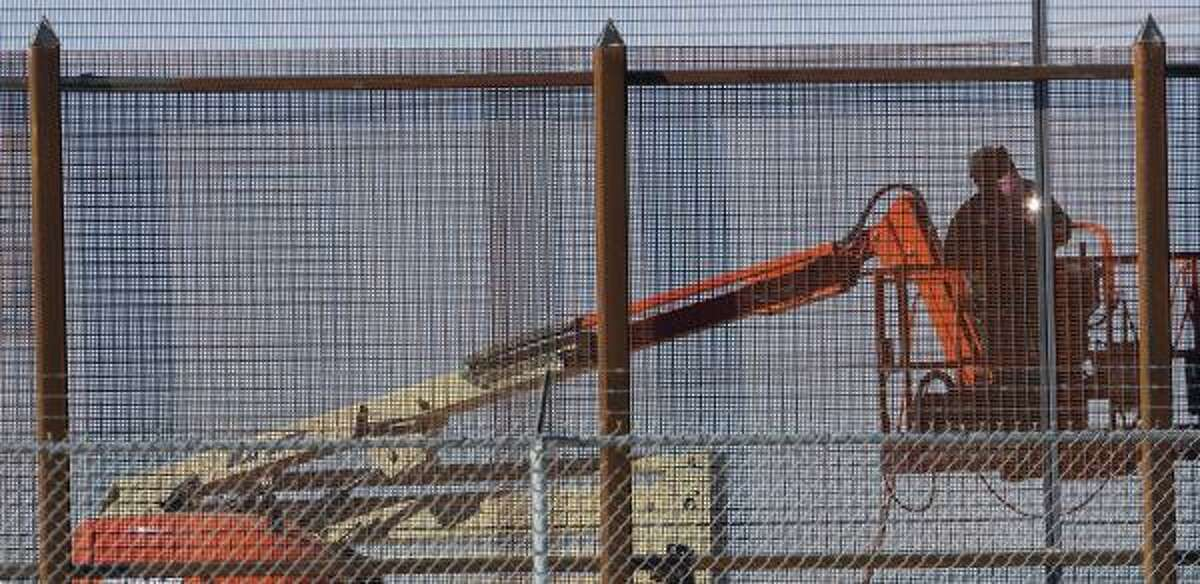 A welder works on a portion of the border fence in El Paso.