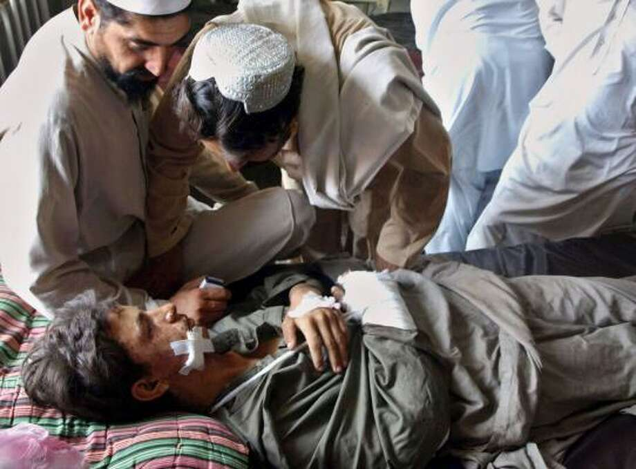A Pakistani tribesman, who was injured in a clash between Afghan forces and Taliban militants, talks with relatives at a hospital in Peshawar, Pakistan, on Wednesday. Photo: MUHAMMAD SAJJAD, ASSOCIATED PRESS