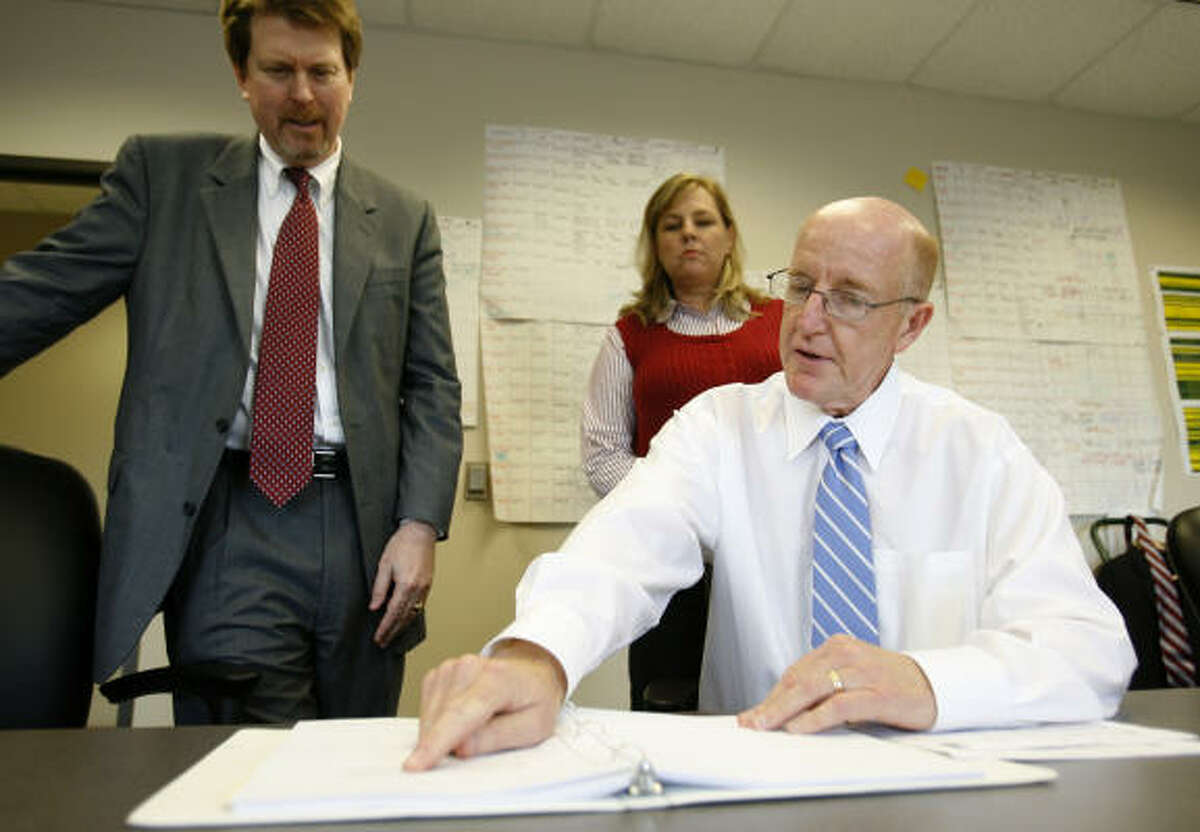 Bob Wicoff, seated, looks over some paperwork with Thomas Martin and Kelly Smith. The three have been appointed to review Harris County cases in which DNA evidence may be key.