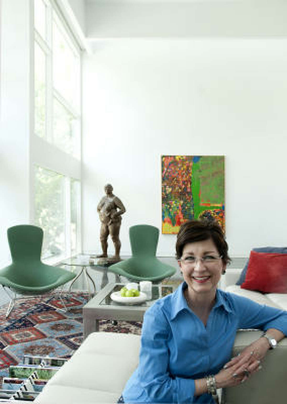 Artist Cara Barer in the living area of her Houston home, which features Francisco Zuniga's bronze sculpture Mujer con Niño en la Cadera (Woman With Child on the Hip) and a large painting by Dick Wray. Bertoia chairs; Roche Bobois sofa; Artemide floor lamp.
