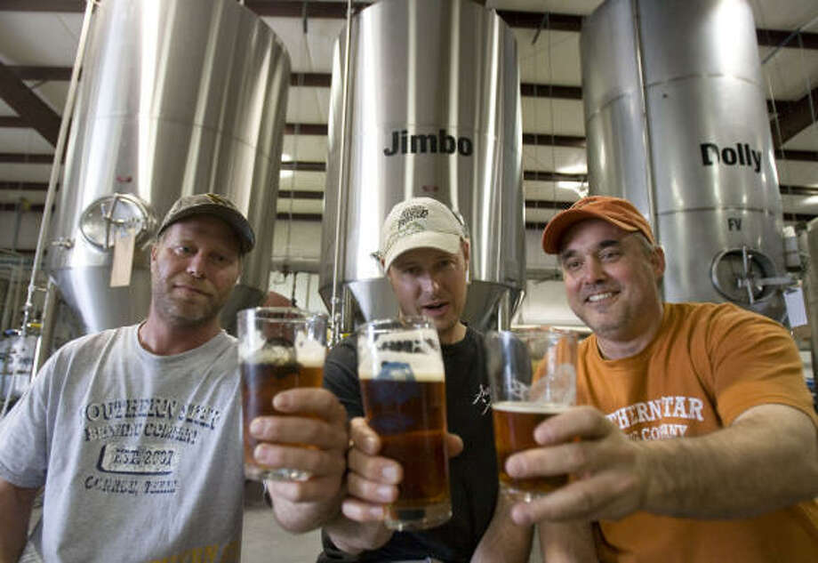 Southern Star founders Brian Hutchins, Dave Fougeron and production guy Joe Hague III raised their glasses in front of the fermenting tanks at Southern Star Brewing Co. The Conroe brewery is celebrating its two-year anniversary this month. Photo: BILLY SMITH II, CHRONICLE
