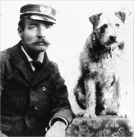 Owney, the Albany postal mascot, poses with an identified Albany postal worker. The orphaned dog was adopted at the Albany post office in 1888 and spent the next nine years traveling the country and world on mail trains as a mascot. (Courtesy National Postal Museum/Times Union archive)