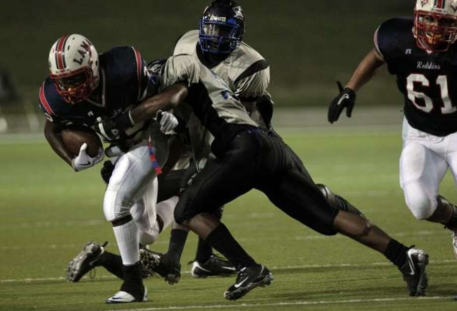 Lamar's London Kirby runs through an attempted tackle by Chavez's Derrick Thompson. Photo: Johnny Hanson, Chronicle
