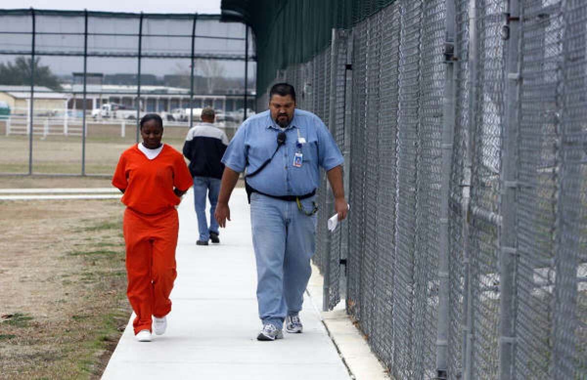 Shaquanda Cotton, left, is led to her dorm by a correctional officer Feb. 23 at the Ron Jackson State Juvenile Correctional Complex in Brownwood.