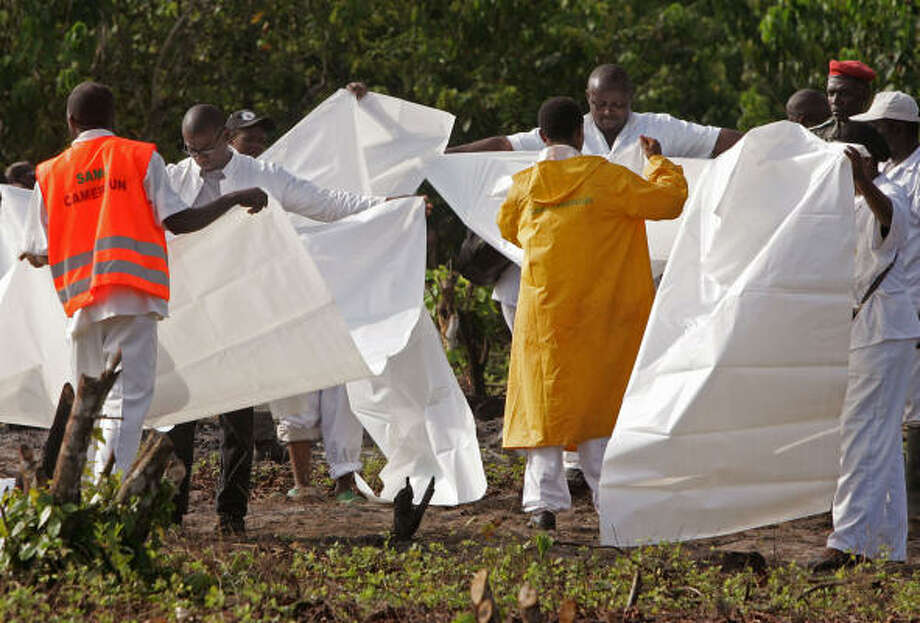 Rescue workers prepare body bags near the crash site of a Kenya airline plane in Mbanga Pongo, Cameroon, on Monday. Aviation officials said Monday that a plane carrying 114 people nose-dived into a thick mangrove forest early Saturday. Photo: SCHALK VAN ZUYDAM, AP