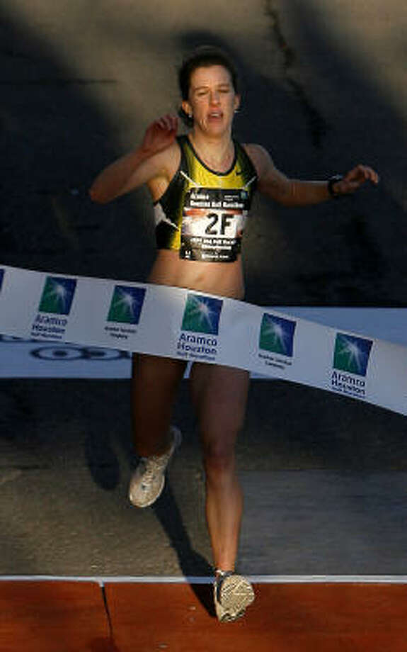Kate O'Neill crosses the finish line as the women's winner of the half marathon. The Chevron Houston Marathon, Aramco Houston Half Marathon and EP 5K run was held early Sunday mornng. Photo: Steve Campbell, Chronicle