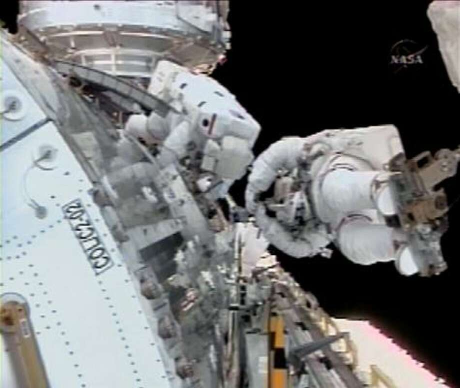 In this image from NASA Television, astronaut Rex Walheim, left, and Stanley Love are seen during a spacewalk to install the Columbus module on the international space station. Photo: AP