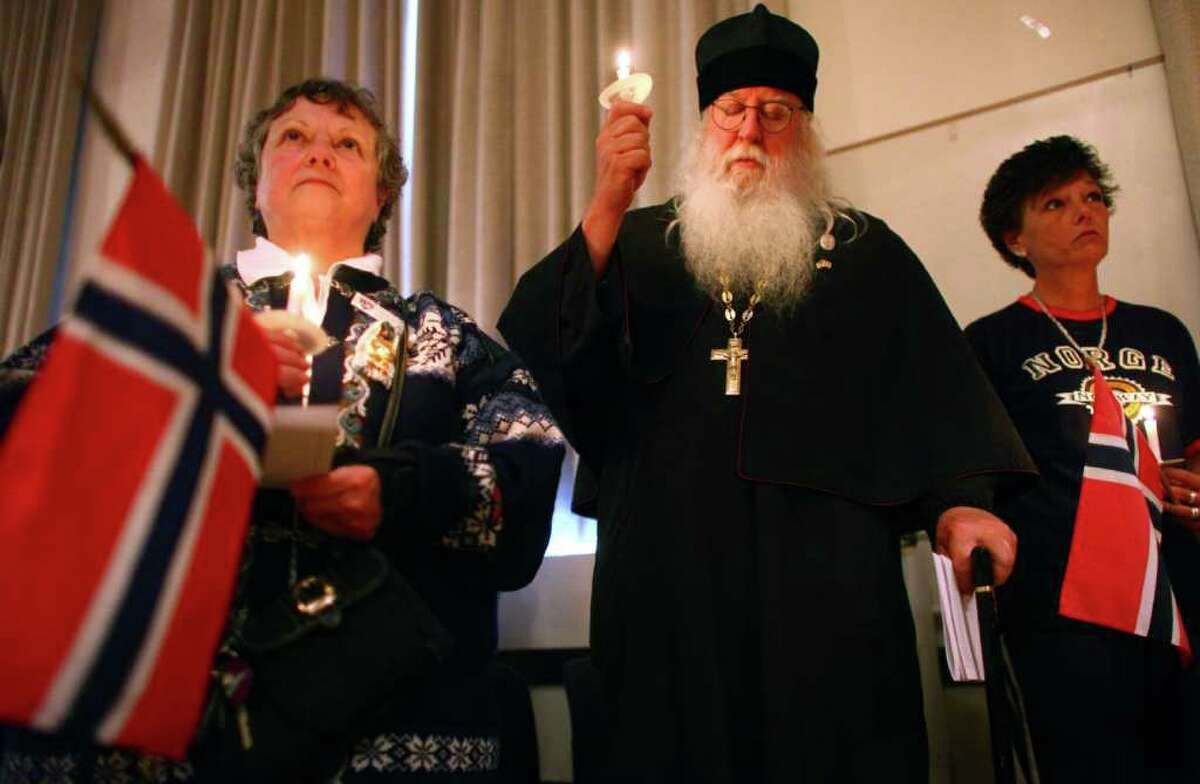 From left, Vicki Nelson of th Sons of Norway in Edmonds, Russian Orthodox Abbott Tryphon, and Sons of Norway member Kirsten Holm participate in a vigil of remembrance at Seattle's Nordic Heritage Museum on Tuesday, July 26, 2011. Seattle's large Nordic population has been shaken by the violent attacks in Norway that killed 76 people, mostly children.