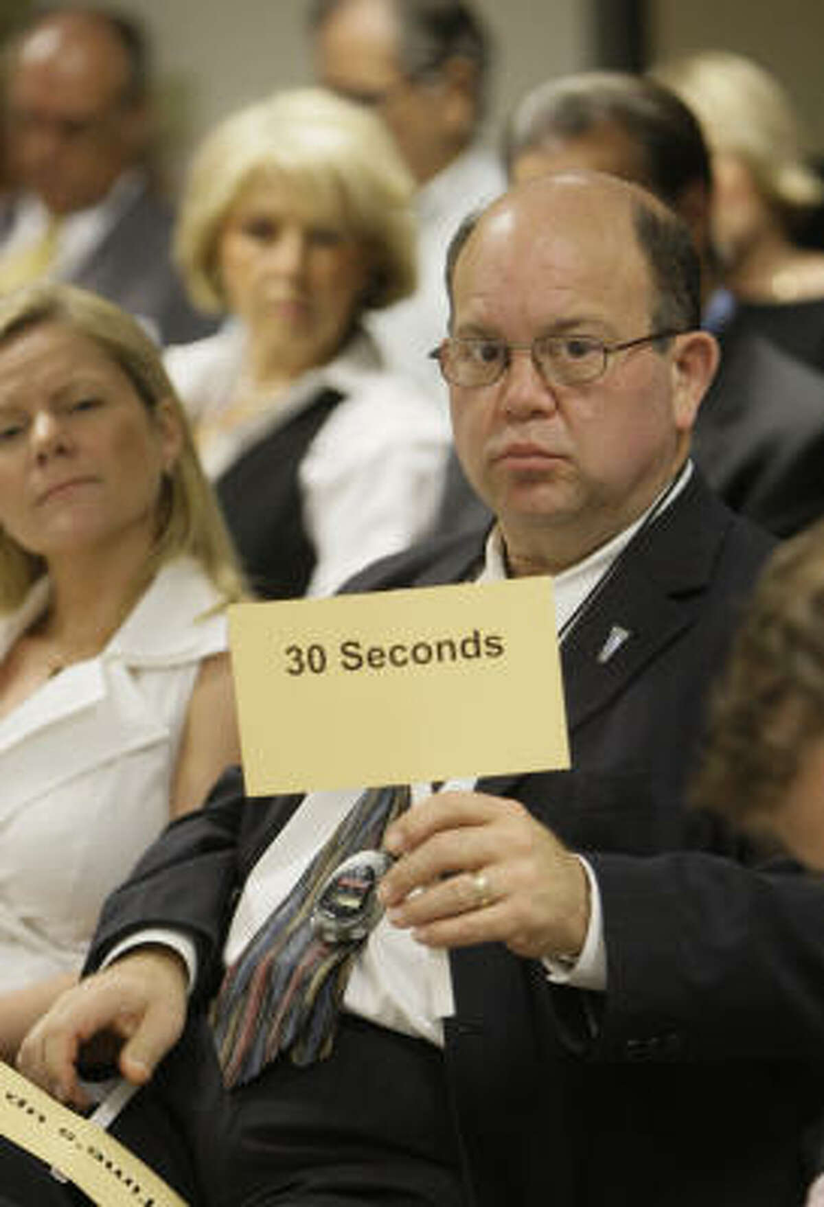 Dave Gilkeson with the Houston West Chamber of Commerce works as timekeeper during a candidate forum Tuesday.