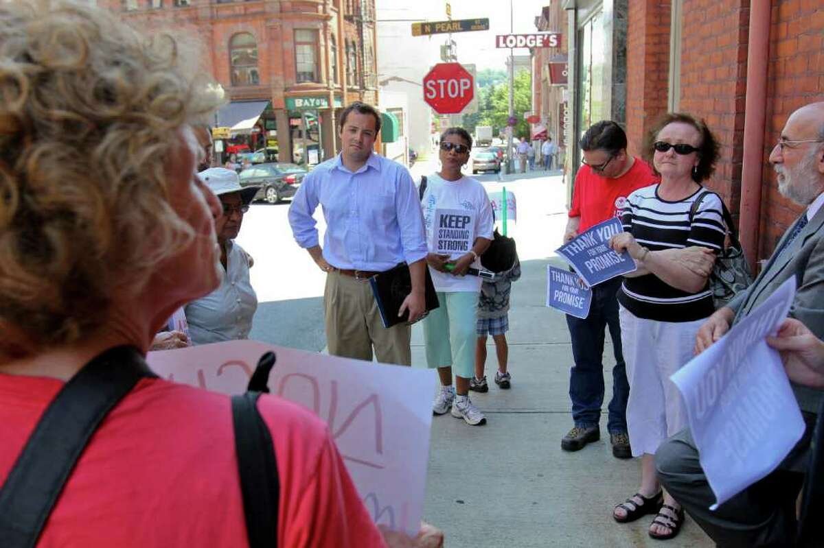 Sean Shortell, District Director of Representative Paul Tonko's Albany office, center, listens to Alice Brody, of Albany, front left, and other participants of a MoveOn.org gathering in front of Tonko's Colombia Street office on Tuesday, July 26, 2011. The group gathered to thank Tonko for his stance against Republican efforts to cut aid to Social Security, Medicare and Medicaid. (Erin Colligan / Special To The Times Union)