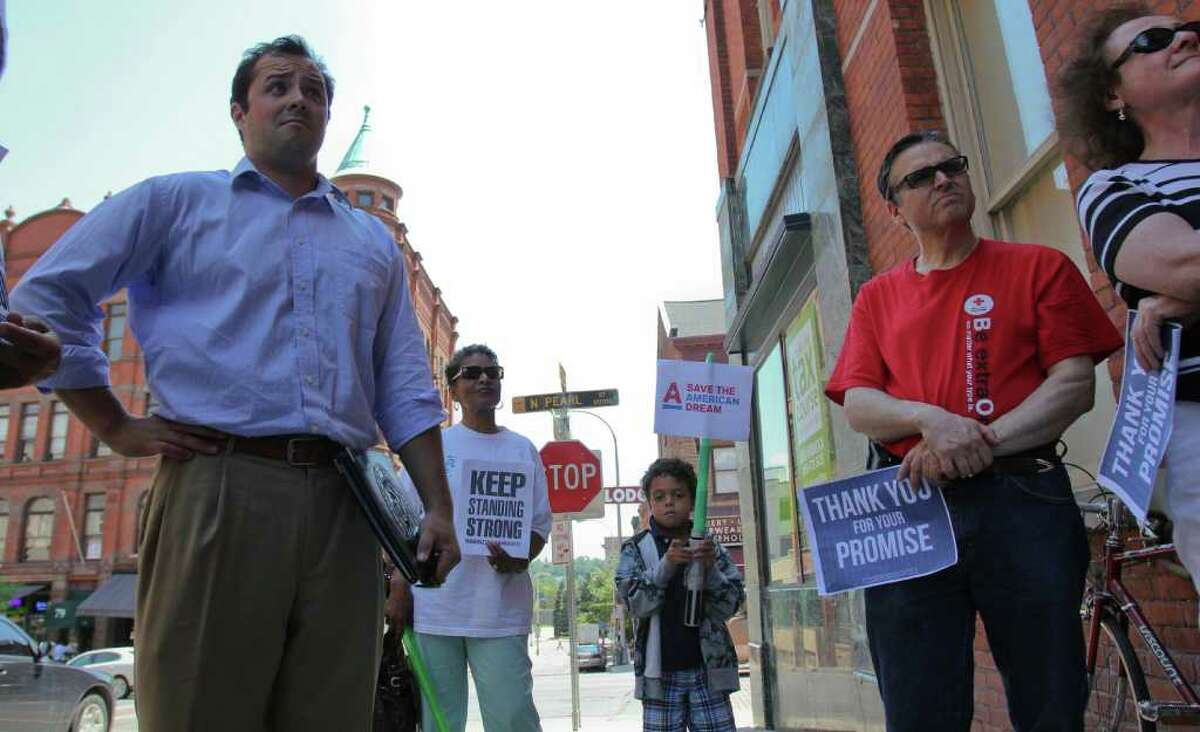 Sean Shortell, District Director of Representative Paul Tonko's Albany office, left, listens to participants of a MoveOn.org gathering in front of Tonko's Colombia Street office on Tuesday, July 26, 2011. Nettie Crossman, of Albany, back left, Jhett Armitage, of Texas, Jonathan Vall, of Albany, and Terri Bronner, of Albany, right, are among the group that gathered to thank Tonko for his stance against Republican efforts to cut aid to Social Security, Medicare and Medicaid. (Erin Colligan / Special To The Times Union)