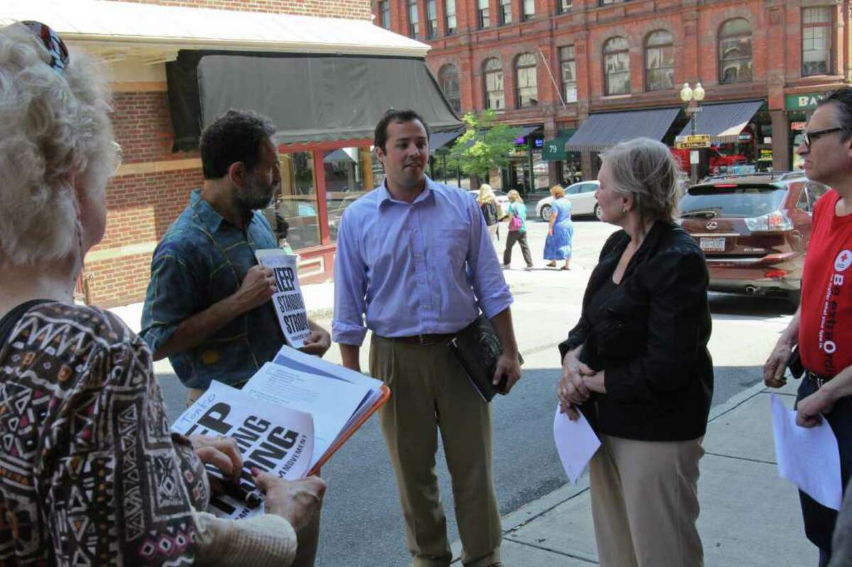Sean Shortell, District Director of Representative Paul Tonko's Albany office, center, listens to participants of a MoveOn.org gathering in front of Tonko's Colombia Street office on Tuesday, July 26, 2011. Kathy Hodges, of Albany, left, Joe Seeman, of Ballston Spa, Lisa Barron, of Loudonville, and Jonathan Vall, of Albany were among the group gathered to thank Tonko for his stance against Republican efforts to cut aid to Social Security, Medicare and Medicaid. (Erin Colligan / Special To The Times Union)