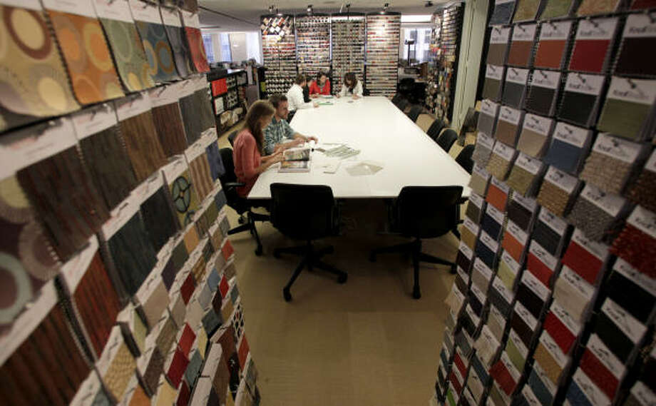 KAREN WARREN : CHRONICLE ALL ON THE TABLE: Staff members work in the resource library, with material samples on the walls, at Planning Design Research Corp. PDR does strategic planning, corporate interior design and research on workplace issues. Photo: Karen Warren, Chronicle