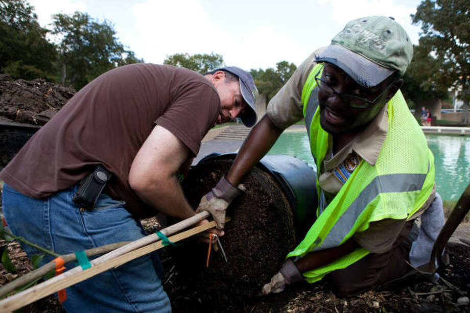 Urban Harvest Executive Director Mark Bowen, left, and James Obryant, of the city's public works department, plant the first tree Saturday in the new City Hall victory garden in Tranquility Park. Photo: Christopher Patronella Jr., Chronicle