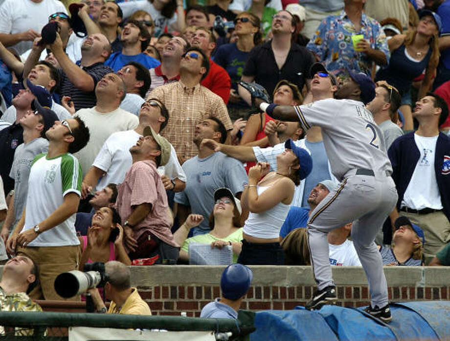 Former Brewers utility player Bill Hall leaps on top of a tarp as he chases a foul ball at Wrigley Field. Photo: JEFF ROBERSON, AP