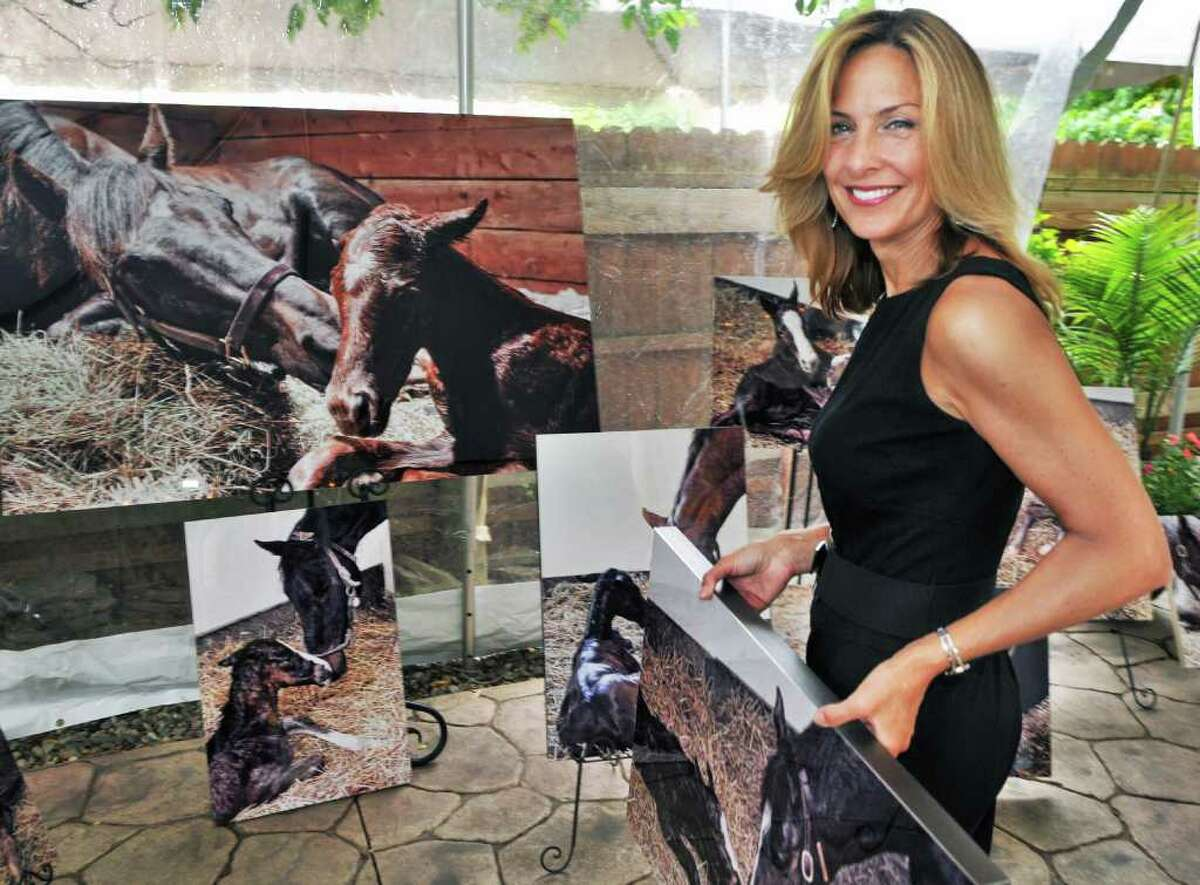 Photographer Lisa Miller of New Hartford, NY, sets up her traveling Foal Project exhibit at Sperry's restaurant in Saratoga Springs Tuesday July 26, 2011. (John Carl D'Annibale / Times Union)