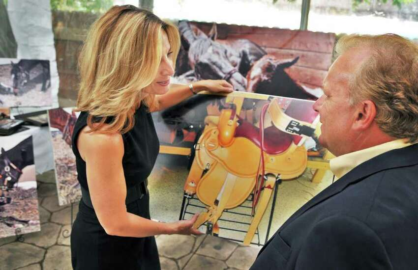 Photographer Lisa Miller, left, of New Hartford, NY, shows an example of an adaptive saddle to Double H Ranch board member Kevin Johnson of Saratoga Springs at her Foal Project exhibit at Sperry's restaurant in Saratoga Springs Tuesday July 26, 2011. (John Carl D'Annibale / Times Union)