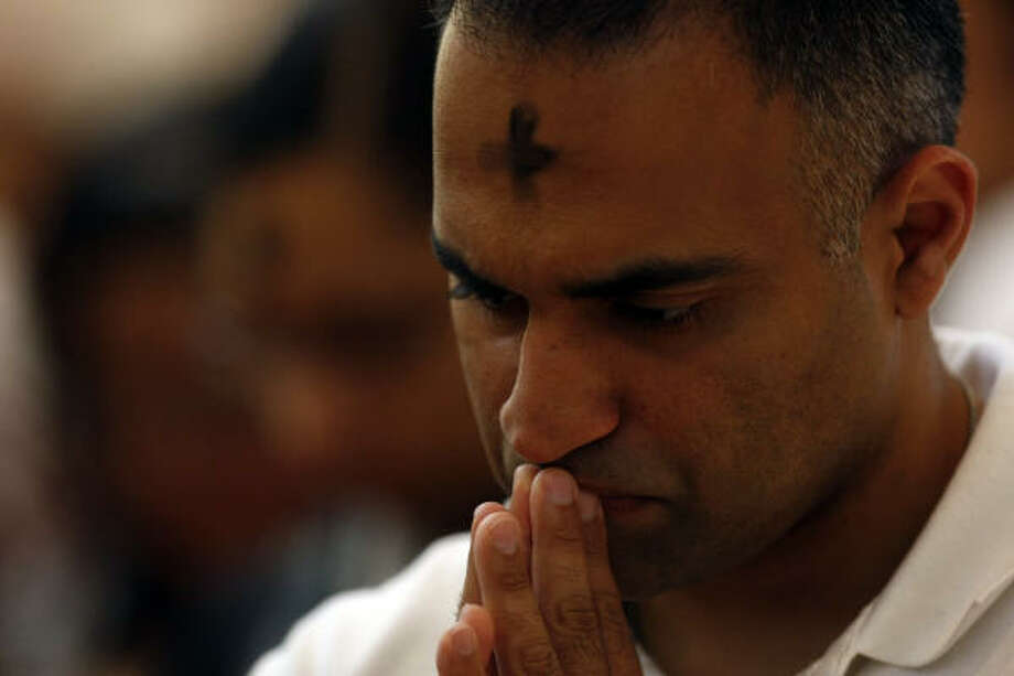 After receiving the sign of the cross in ashes on her forehead, Manoj Kurian prays during mass at the Co-Cathedral of the Sacred Heart Catholic Church. Photo: Johnny Hanson, Chronicle