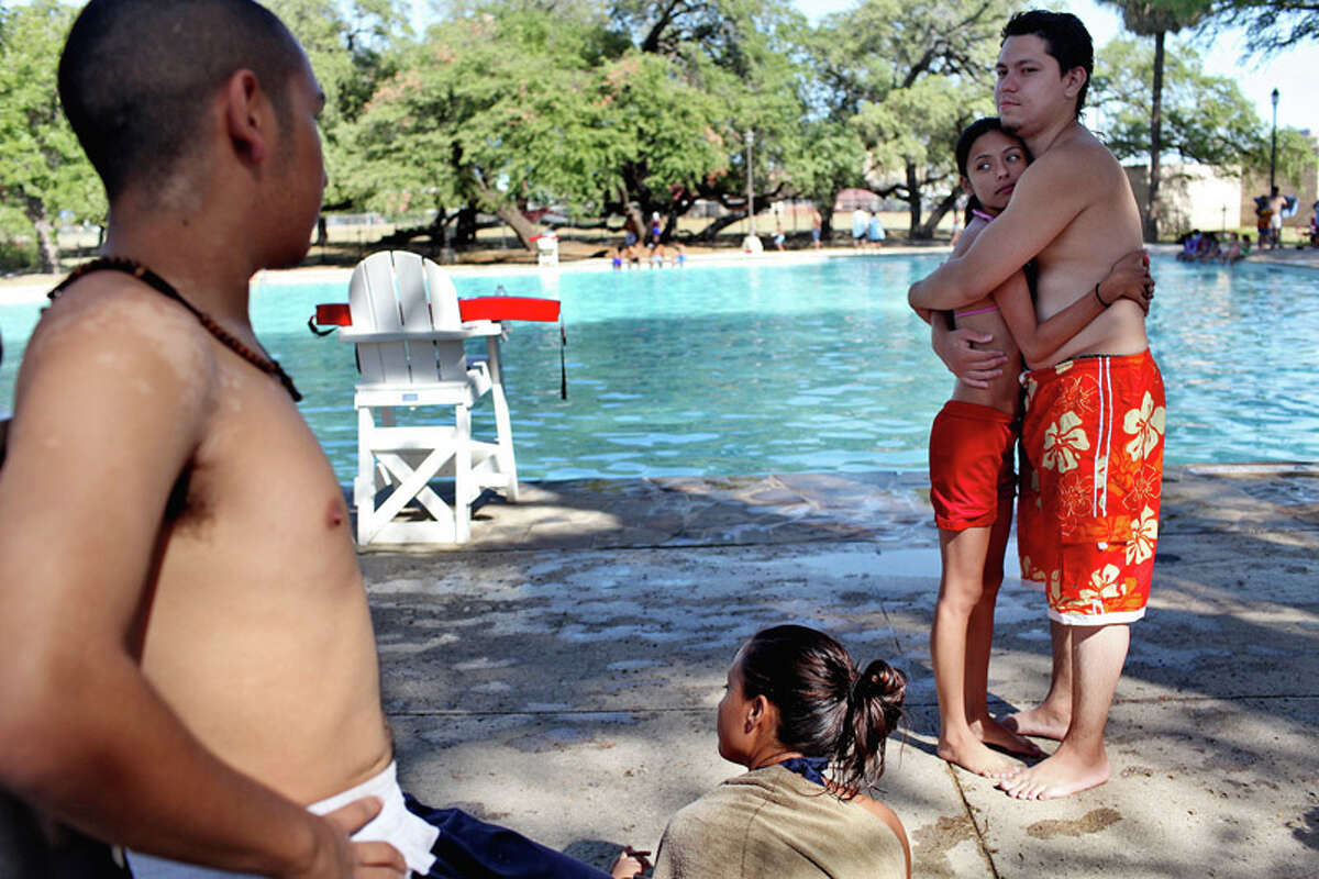 Norma Contreras (right) embraces her boyfriend, Eliezer De La Torre, next to her sister, Rosa Contreras (center), and Edgar Gavino (left), during a swimming break at the San Pedro Springs Park pool in San Antonio on July 26, 2011.