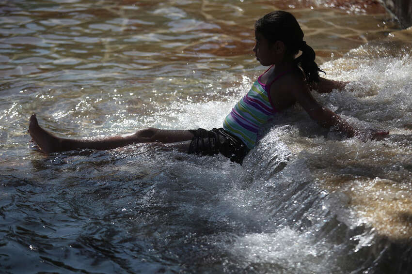 Kimberly Uranga, 9, rests in the water as she swims in the San Pedro Springs Park pool in San Antonio on July 26, 2011.