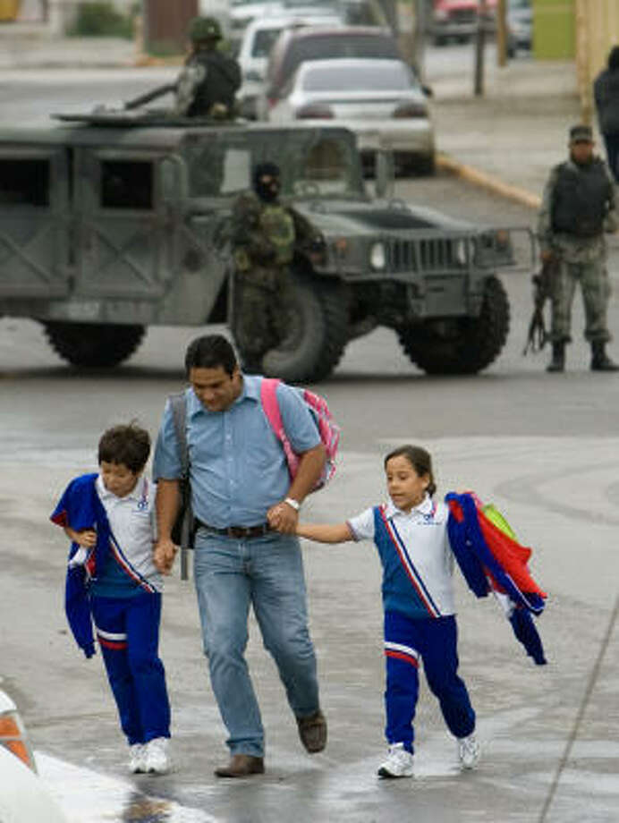 A man and his children scramble for safety near the Carrillo Puerto Primary School. Photo: Alex Jones, AP