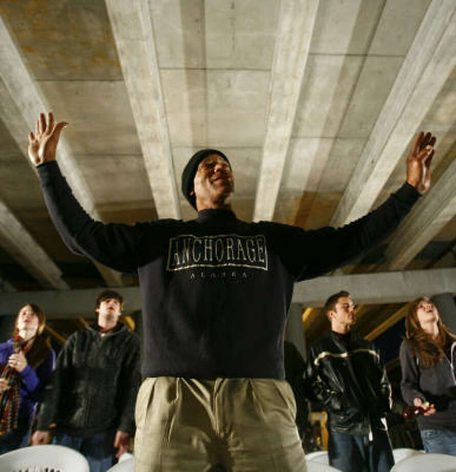 Leonard Payne raises his hands in praise as he and about 80 others gather for a recent service of the Church Under the Bridge at Pierce and Bastrop. The church service is held for homeless people and often distributes food, clothing and other essentials. Photo: Michael Paulsen, Chronicle