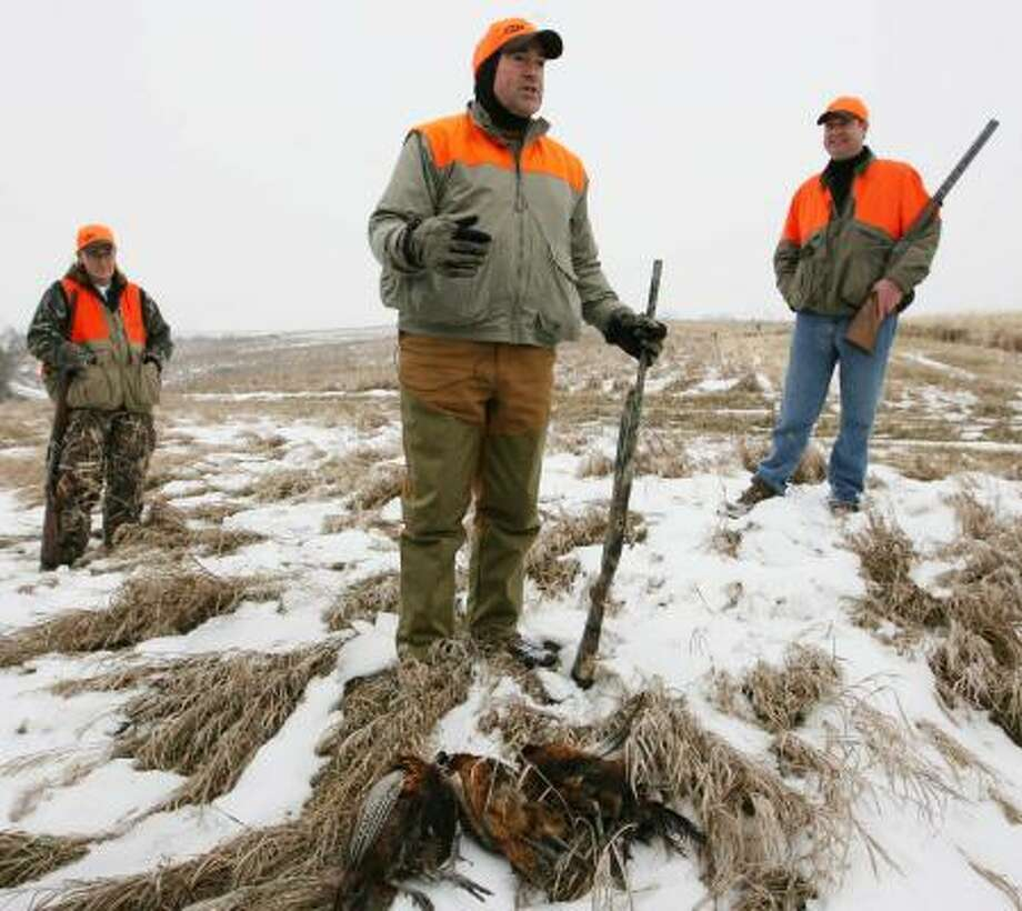 Mike Huckabee talks to the media in a field near Osceola, Iowa, after he and Andrea Cerwinske, left, of the National Rifle Association, and his campaign manager Chip Saltsman bagged three pheasants. Photo: JOHN GAPS III, DES MOINES REGISTER