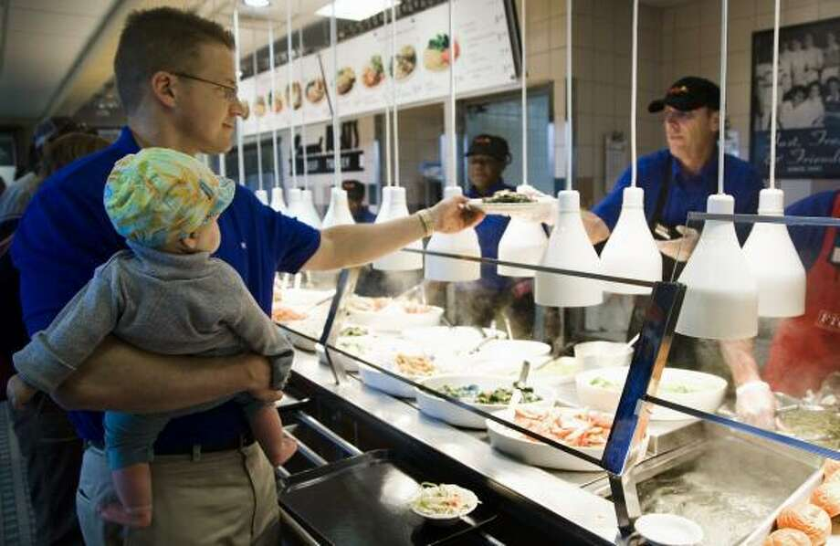 Matt Soper holds his niece, Meredith Yates, as he moves through the line at a Luby's in 2008. Photo: SMILEY N. POOL, CHRONICLE