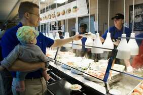 Matt Soper holds his niece, Meredith Yates, as he moves through the line at a Luby's in 2008.