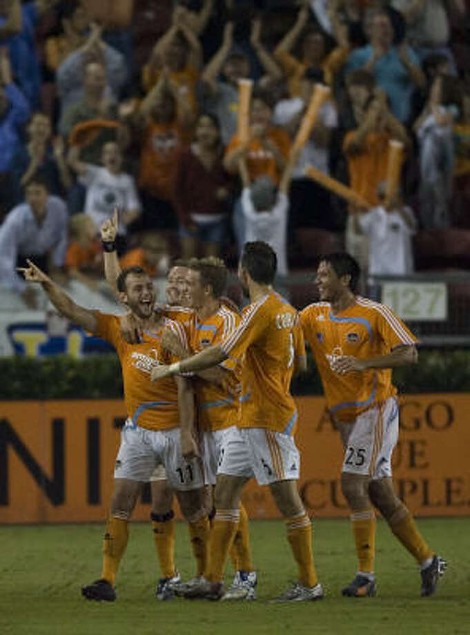 The Dynamo's Brad Davis (11) celebrates with teammates after he scored unassisted in the 100th minute of a 4-1 win over FC Dallas last season. Photo: Smiley N. Pool, Houston Chronicle