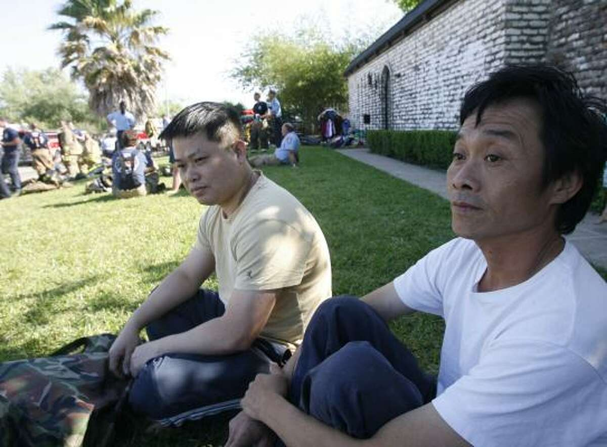 Tien Van Nguyen, right, and Andy Truong sit Saturday after the fire at Linda Square Apartments in Houston.