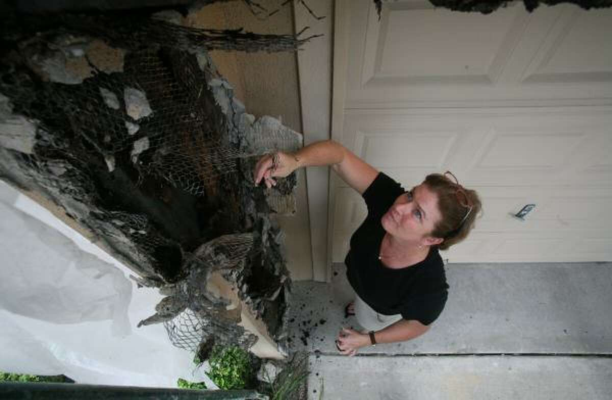 Sarah Reid Ford looks at damage to a neighbor's condominium. The disgruntled West Clay Street homeowner is bitter that the District Attorney's Office won't pursue criminal charges against the builder.