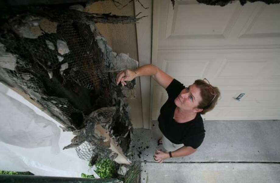Sarah Reid Ford looks at damage to a neighbor's condominium. The disgruntled West Clay Street homeowner is bitter that the District Attorney's Office won't pursue criminal charges against the builder. Photo: STEVE CAMPBELL, CHRONICLE