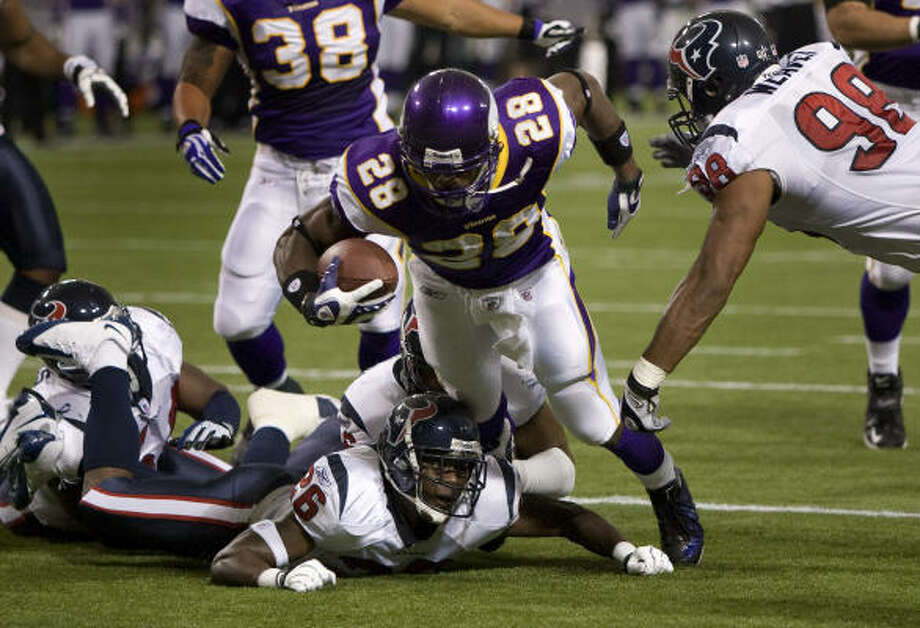 Minnesota running back Adrian Peterson (28) runs over Texans cornerback Eugene Wilson as he nears the goal line during the first quarter of the Vikings' win Sunday. Photo: Brett Coomer, Chronicle