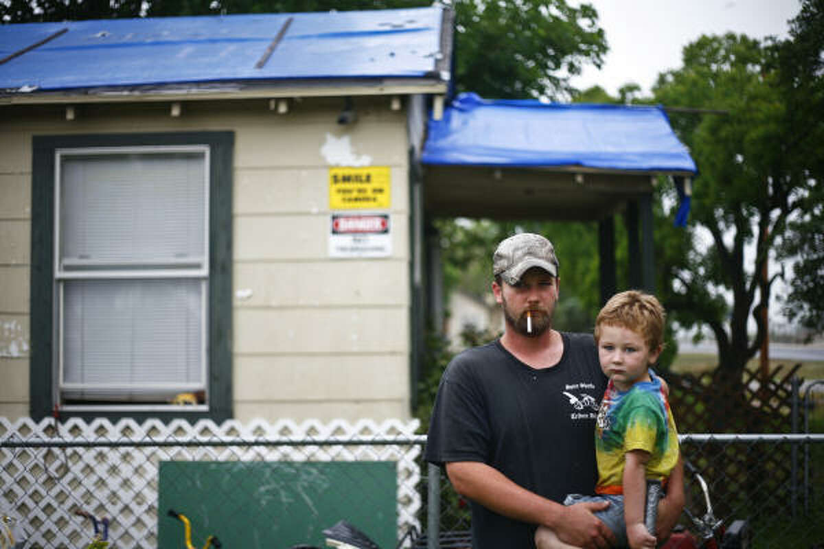 Clark Daymude holds his son Case, 3, in front of their home that still has a blue tarp protecting the roof damaged by Hurricane Ike. He wasn't aware of the federal aid now available.