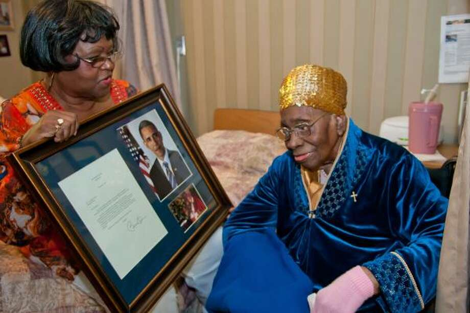 Autrey Stewart Dunlap held a letter from President Obama congratulating Louvenia Posey on her 111th birthday in 2011. She celebrated the big event at the Windsong Village Convalescent Center in Pearland. Photo: Kim Christensen, For The Chronicle