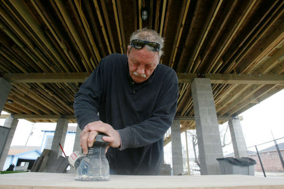 James Hair works on what will be a centerpiece for a counter at his sister Tanya Fabian's house in Bayou Shores. The siblings have dipped into their savings in order to bring the home back into shape after it was destroyed during Hurricane Ike. Photo: Julio Cortez, Chronicle