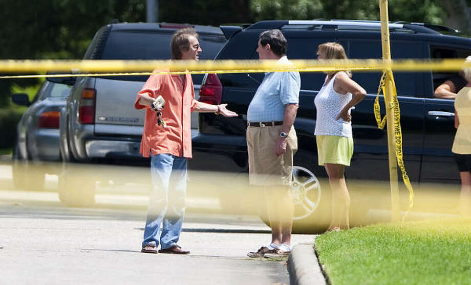 Volker Maerz, left, chats with neighbors as authorities investigate a house where a pregnant woman was shot and killed Sunday morning in northern Harris County. Neighbors say the married woman was to soon give birth to a girl. Photo: Nick De La Torre, Chronicle