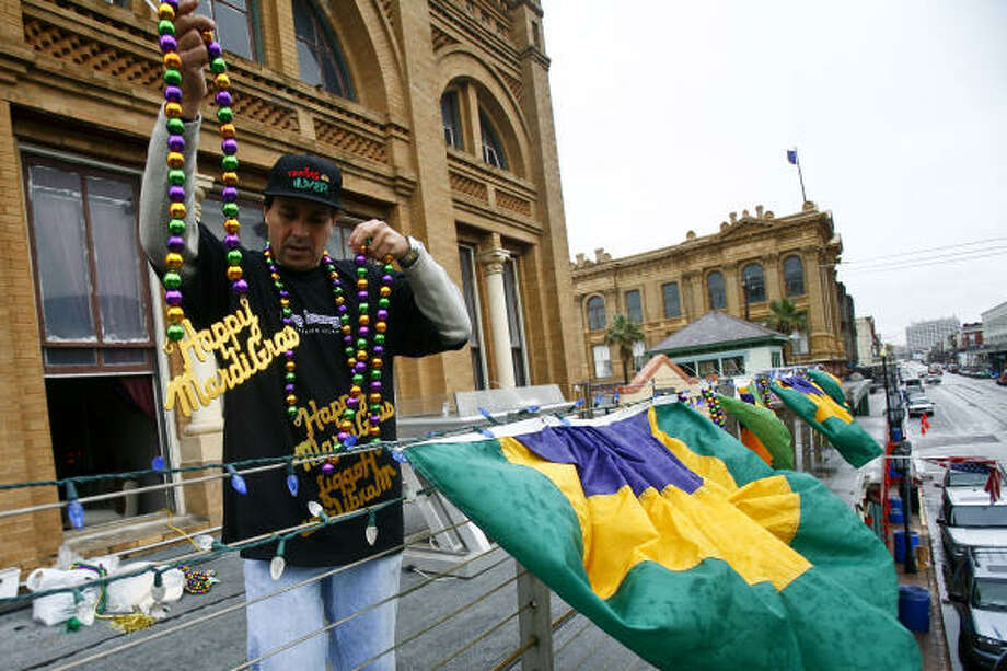 """Allen Flores, president of the Strand Merchants Association, hangs beads from his balcony in Galveston on Thursday in preparation for the celebration that begins today. """"I think the word is out that we are back and ready to go,"""" he said. Photo: Michael Paulsen, Chronicle"""